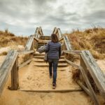 picture of woman walking up stairs at the beach